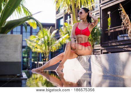Woman sunbathing in bikini at tropical travel resort. Beautiful young woman lying near pool