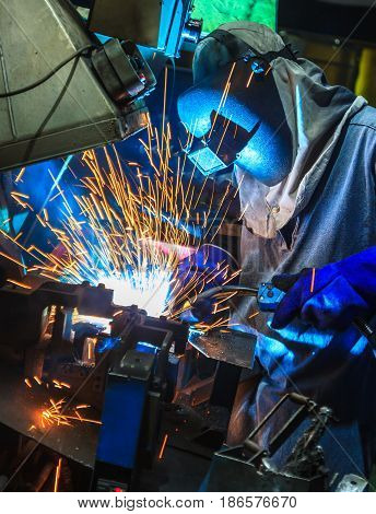 Worker,welding in a car factory with sparks, manufacturing, industry