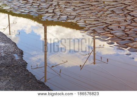 The railroad's electric line with a blue sky and clouds is reflected in a puddle. Old paving stones.