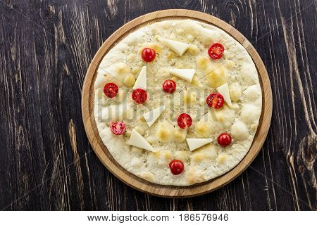 Traditional Italian bread focaccia with cheese and cherry tomatoes over wooden background