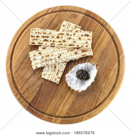 Black sturgeon caviar and matzah on cutting board view from above. With clipping path.