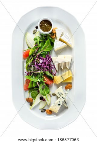 Selection of different kinds of cheese with greens and fruit. With clipping path view from above.