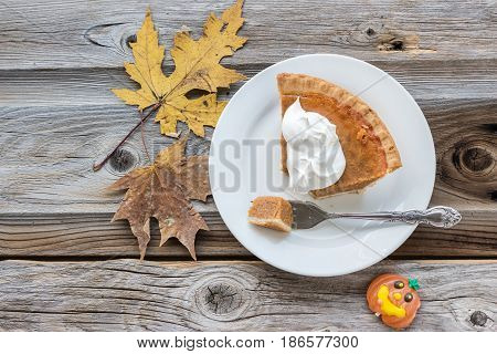 horizontal image of a sweet and spicy pumpkin pie topped with whipped cream with a piece cut with fork on a wood surface and background adorned with maple leaves and a pumpkin candy.