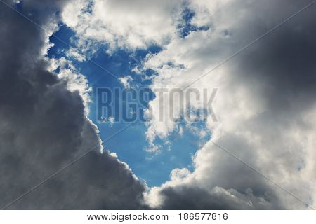 Background. White gray and black clouds in the sky created an empty place in the blue sky.