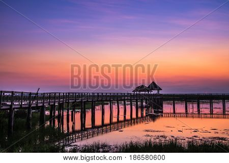 View of swamp and wooden pavilion and bridge during sunset in rural of Thailand