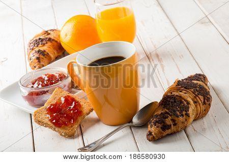 croissant  mug of coffee orange juice and toast with jam