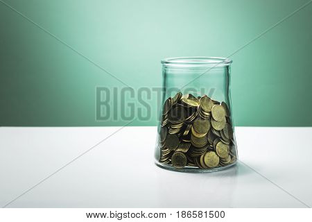 money in a glass bottle on white table and green wall background savings concept