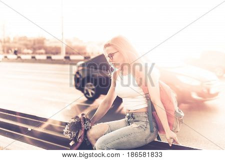 Young attractive hipster girl hitchhiking sits on the highway fence and holds a bouquet of lilac flowers. She is dressed in top and jeans. Backlight photography. Road adventures