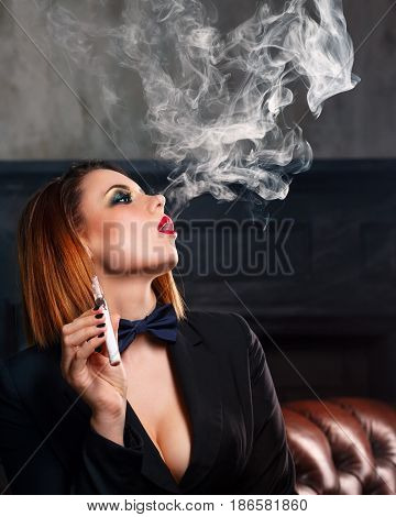 Young attractive girl in a jacket and bow tie smokes electronic cigarette. Femme fatale. Evening makeup smokey eye. Delicious steam.