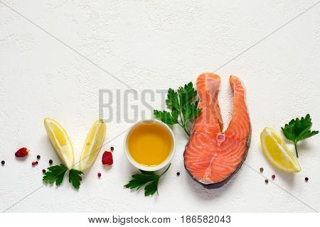 Fresh raw salmon steak, olive oil, lemon and spices on a white background. Top view with copy space