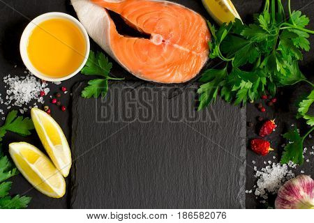 Fresh raw salmon steak And ingredients for preparation around the cutting board. Top view with copy space