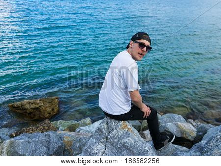 Wondered man with opened mouth is sitting on the rock and looking at the camera