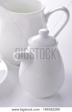 White porcelain sauceboat and creamer close-up on gray background