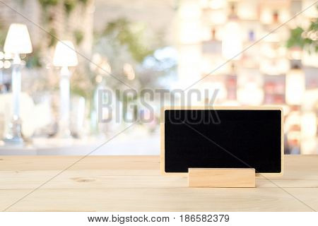 Blank chalkboard standing on wood table over blur restaurant with bokeh background space for text mock up product display montage