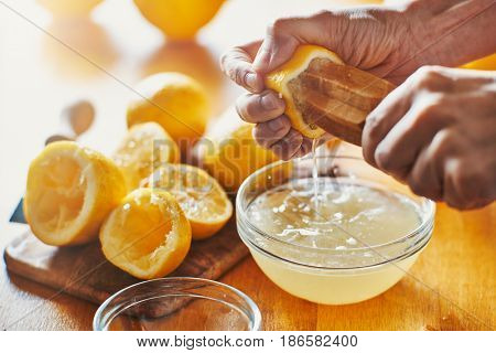woman's hand squeezing juice from a lemon with wooden tool