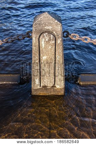 A concrete pylon maintains a barrier along the St. Croix River in Stillwater Minnesota despite floodwaters creeping in.