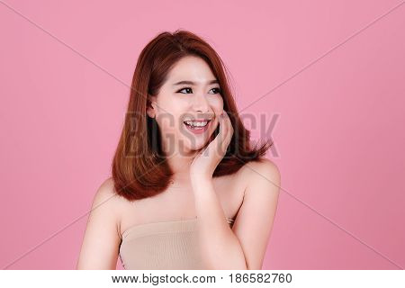 Short Hair Asian Young Beautiful Woman Smile And Point On Her Head, Isolated Over Pink Pastel  Backg