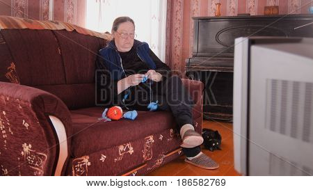 Portrait of an elderly woman in glasses and a home clothes, which sidin on a brown sofa in front of the TV and knit colored threads on the spokes. Next to the sofa lying on her back black cat.