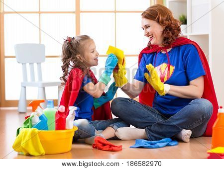 Happy woman with child daughter cleaning room and having fun playing at home. Family housework conception.