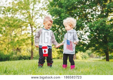 Happy adorable little blond Caucasian girl and boy smiling laughing holding hands and waving American and Canadian flags outside in park celebrating 4th july Independence Day