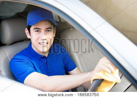 Male staff cleaning car steering wheel with microfiber cloth - auto detailing concept