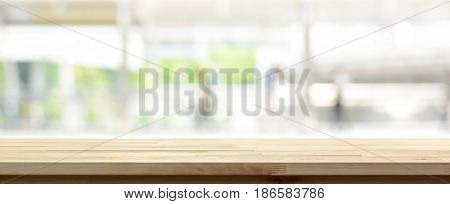 Wood table top on blur kitchen window background panoramic banner - can be used for display or montage your products (or foods)