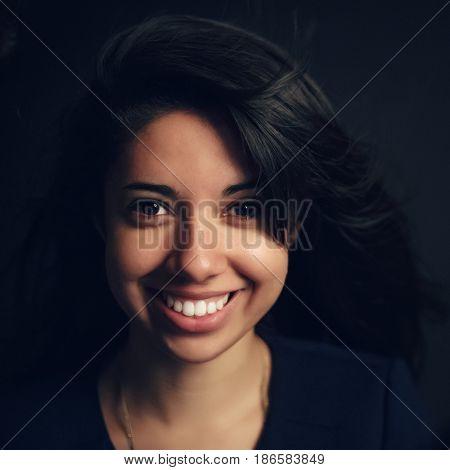 Portrait of beautiful smiling Hispanic latino girl woman with dark brown eyes long dark hair in white shirt posing in studio on dark black background looking in camera