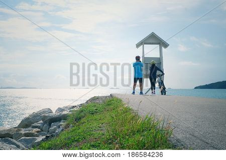 Couple cycling with Seascape view of lifeguard tower and clear blue sky for relaxing at Khao Laem Ya National Park, Rayong, Thailand.