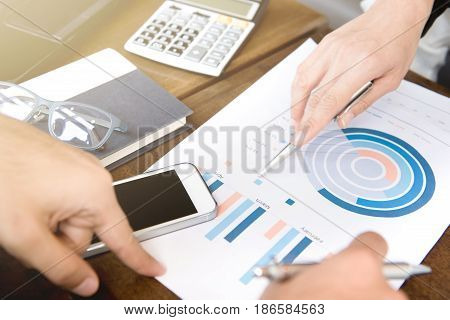 Business people discussing and analyzing financial document