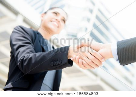 Businesswoman making handshake with a businessman - greeting dealing merger and acquisition concepts