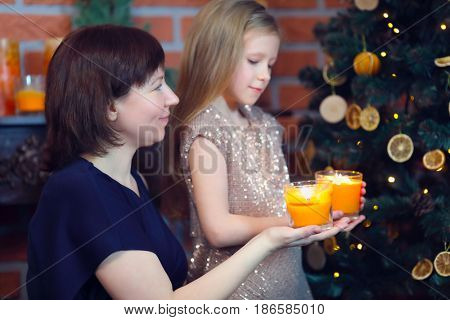 Woman and her little daughter hold candles near christmas tree in room, focus on mother