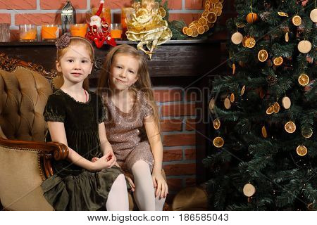 Two happy little girls pose in armchair near christmas tree in room