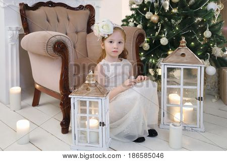 Little girl in white sits near armchair in room with christmas tree and lanterns on floor