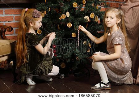 Two happy little girls decorate christmas tree with dried orange in stylish room