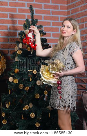 Blonde woman in short dress decorates christmas tree in brick studio