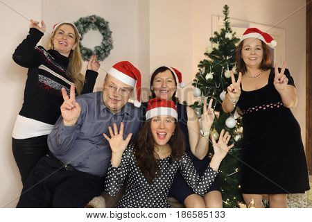 Five people in santa caps pose near near christmas tree, focus on man and woman in middle