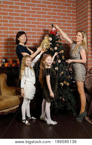Two women with two daughters decorate christmas tree in stylish studio