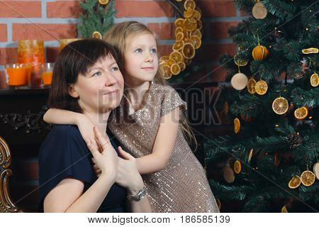 Woman and her little daughter embrace and look away near christmas tree in room, focus on mother