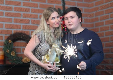 Woman with doll and her son teenager with sparkler pose in room with christmas tree
