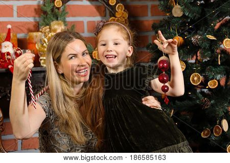Happy woman with little daughter pose near christmas tree in room