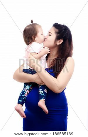 Young asian mother is pregnant hugging kid in the arms and kiss lip her daughter on white background with family concept