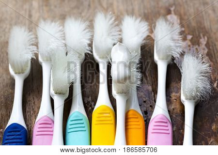 Old toothbrushes on wood table concept toothbrush wear and tear.