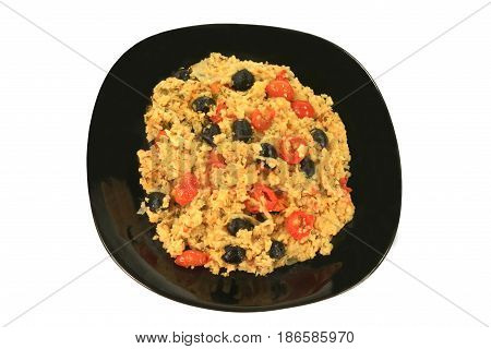 Healthy Vegetarian Mediterranean Style meal of rice onion small cherry tomatoes (cut in half and whole) black olives seasoned with parsley flakes and red pepper served on a black porcelain dish