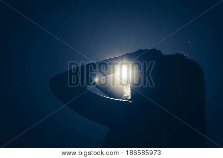 Silhouette Of Depress Woman Standing In The Dark With Light Shine Behind
