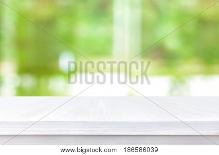 White wood table top on blur green abstract background - can be used for montage or display your products