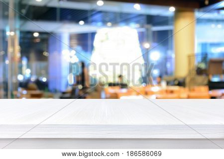 White wood table top on blur background of coffee shop interior - can be used for display or montage your products