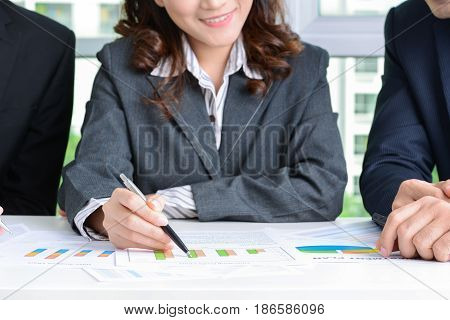 Businesswoman and businessmen discussing graphs at meeting table