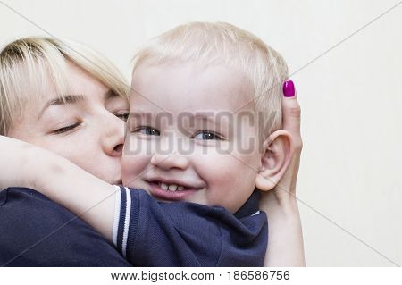 Happy mother with eyes shut hugging and kissing her little son who looking at camera