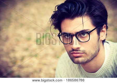 Close-up portrait of a handsome young man with glasses. Attractive and charming man with fashionable hair. Short beard. Outdoors.