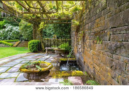 Renaissance Lion Head water fountain on a stone block wall with stone steps bench manicured garden